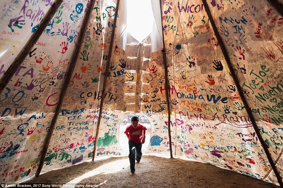 For nearly ten months, members of the Native American Standing Rock Sioux tribe and their allies have been camped here in opposition to the Dakota Access Pipeline crossing their land and water. Pictured here, 12-year-old Jesse Jaso enters their Unity Teepee, which has been signed by camp supporters from all over North America and the rest of the world