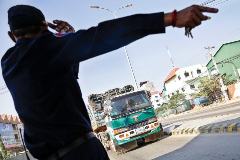 An official directs a truck toward a toll booth on Veng Sreng Boulevard yesterday.