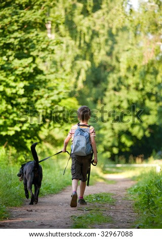 Young boy walking with black dog - stock photo
