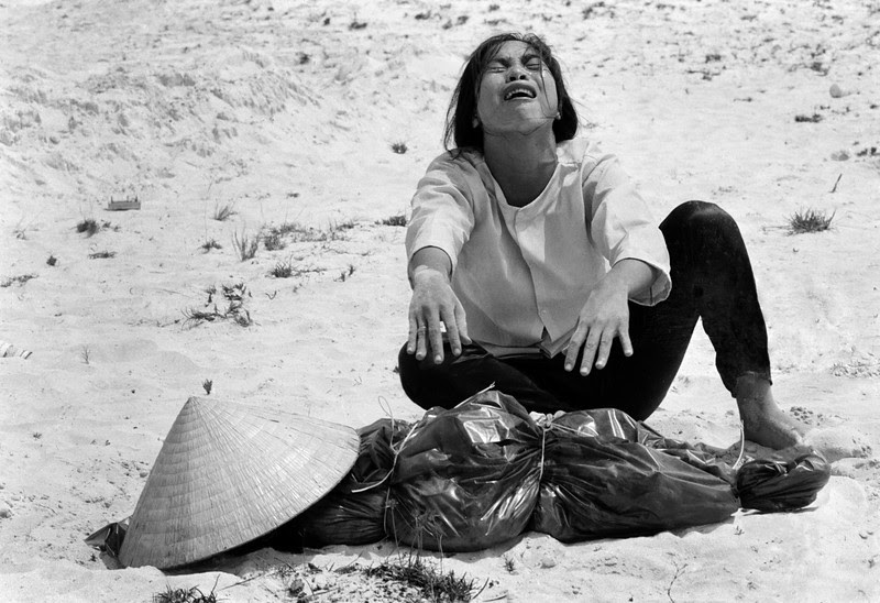 Description of  A South Vietnamese woman mourns over the body of her husband, found with 47 others in a mass grave near Hue, Vietnam in April of 1969. (AP Photo/Horst Faas, File)