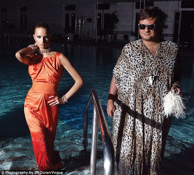 Arrefecer: Em outro estalo abafado, Karolina emerge de uma piscina em um vestido de noite de laranja, ao lado de uma fashionista masculino ostentando um leopardo kaftan