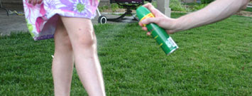 Photo: Woman spraying insect repellent on arm