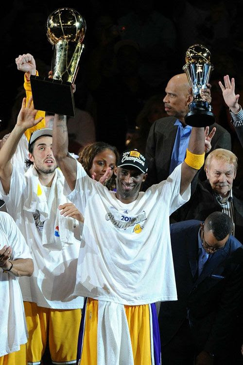 Kobe Bryant hoists up the NBA championship trophy and his 2nd Finals MVP trophy after he leads the Lakers to its 16th title, on June 17, 2010.