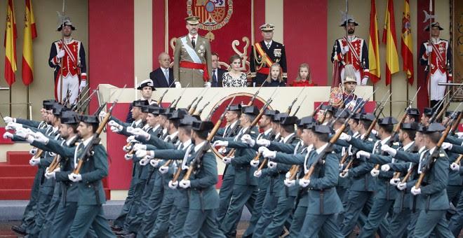 El rey Felipe VI, acompañado de su familia, presencia el paso de una unidad de la Guardia Civil durante el desfile militar del 12-O de 2016. JUANJO MARTÍN/EFE