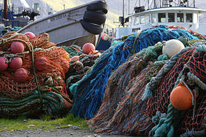 Fishing boats and piled nets at Dutch harbor, ...