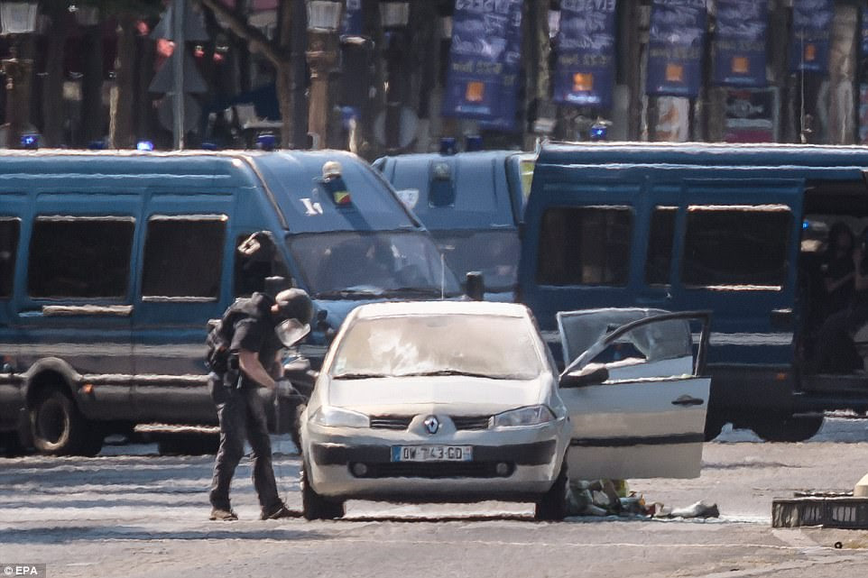 The car being searched by a member of the bomb disposal team who is seen approaching the Renault Megane with a mask