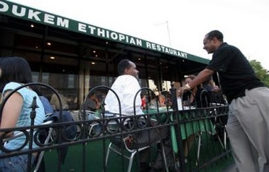 Tefera Zewdie talks to guests outside his restaurant Dukem in Washington,
