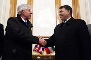 Former British foreign secretary Jack Straw (L) shakes …