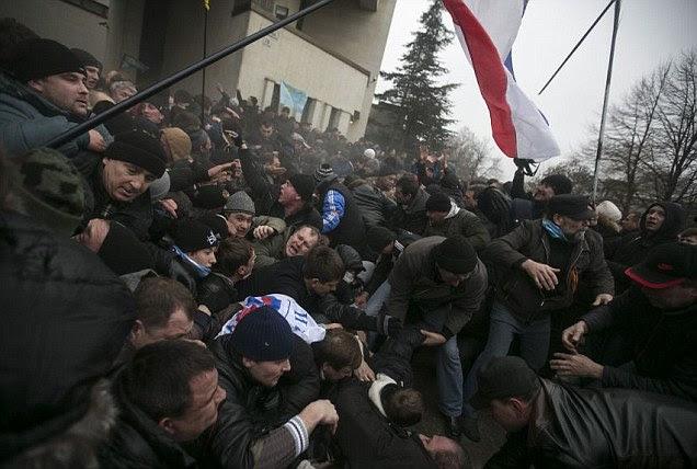 Hommes ukrainiens aider à tirer l'autre sur une ruée comme un drapeau de la Crimée est vu lors d'affrontements à rassemblements organisés par les Russes ethniques et les Tatars de Crimée près du bâtiment du Parlement de Crimée