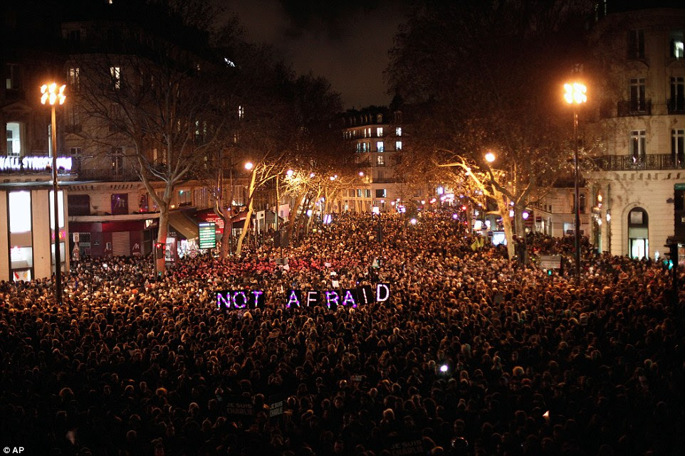 'Not afraid': People gather to pay their respects for the victims of the terror attack against the satirical newspaper, in Paris tonight