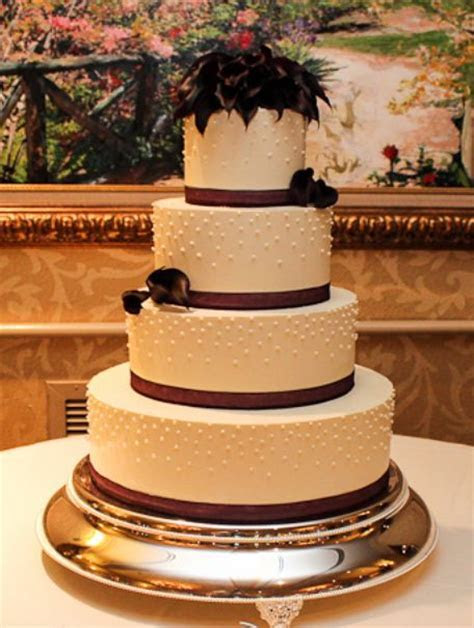 4 tier round white wedding cake with black flowers on top