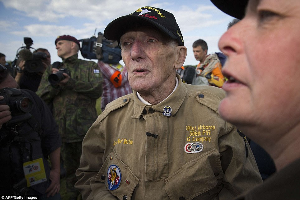 Hero: US war veteran Jim 'Pee Wee' Martin (center), 93, looks on after landing with a parachute on June 5, 2014 over Carentan, where he landed 70 years ago, when he was a paratrooper