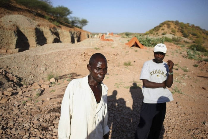 George Mwangi, left, and Joel Warvare Karinga search for their belongings after surviving an attack by al-Shabaab militants that left 36 non-Muslim workers dead at a quarry near the town of Mandera at the Kenya-Somalia border