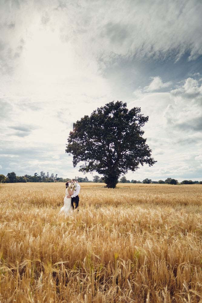 bride and groom  in field with tree with dramatic sky, Suffolk wedding photos, suffolk wedding - www.helloromance.co.uk