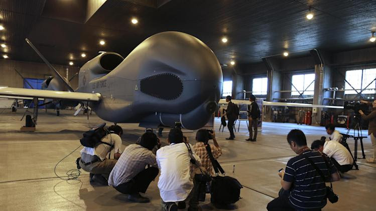 Japanese journalists gather around an advanced Global Hawk surveillance drone in its hangar at Misawa Air Base in northern Japan, Friday, May 30, 2014. The U.S. Air Force has deployed two of the unarmed Global Hawk aircraft to Japan for the first time over the past week to enhance the U.S. military's efforts to monitor nuclear activities in North Korea, Chinese naval operations in the region and assess natural disasters to assist humanitarian aid operations. (AP Photo/Eric Talmadge)