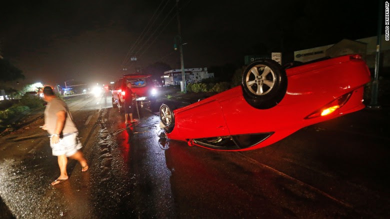 People tend to a car that flipped over on Cape Coral Parkway during Hurricane Irma, in Cape Coral, Florida, on Sunday, September 10. Irma made its second landfall in the state Sunday afternoon on nearby Marco Island as a dangerous Category 3 storm.