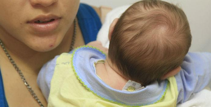 Imagem de mulher segurando bebê com microcefalia (Foto: Fernando da Hora / JC Imagem)