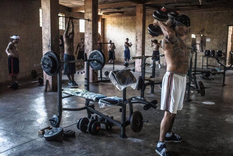 Et medlem af Mara Salvatrucha dyrker styrketræning i et sparsomt indrettet træningslokale i fængslet i Ciuda Barrios i El Salvador. (Foto: All Over Press)