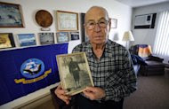 In this Nov. 29, 2011, photo, World War II Navy veteran Clarence Pfundheller poses at his Greenfield, Iowa, apartment with a photo of himself taken during basic training in 1939. Now 91, Pfundheller will be returning to Pearl Harbor on Wednesday, Dec. 7, 2011, for the 70th anniversary ceremony honoring those lost in the Dec. 7, 1941 attack that brought the United States into World War II. Accompanying him will be fellow survivors, other World War II veterans, and a handful of college students to hear their stories. (AP Photo/Charlie Neibergall)