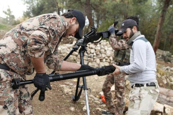 Rebel fighters prepare to fire a machine gun towards forces loyal to Syria's President Bashar al-Assad in the Jabal al-Akrad area in Syria's northwestern Latakia province November 25, 2014. REUTERS-Alaa Khweled