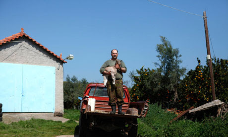 George Andrianakis, 56,poses with a goat in the yard of his farm in the village of Stafania, Greece.
