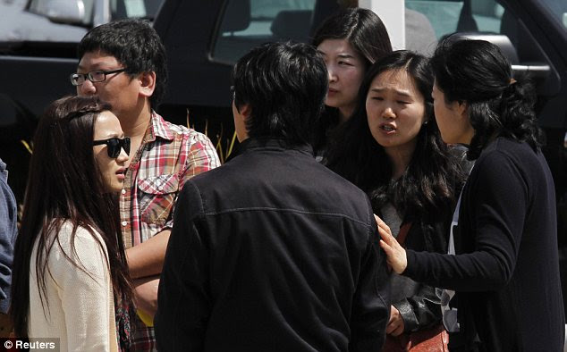 Mourners: Students talk among themselves at the scene of the deadly shooting on Monday