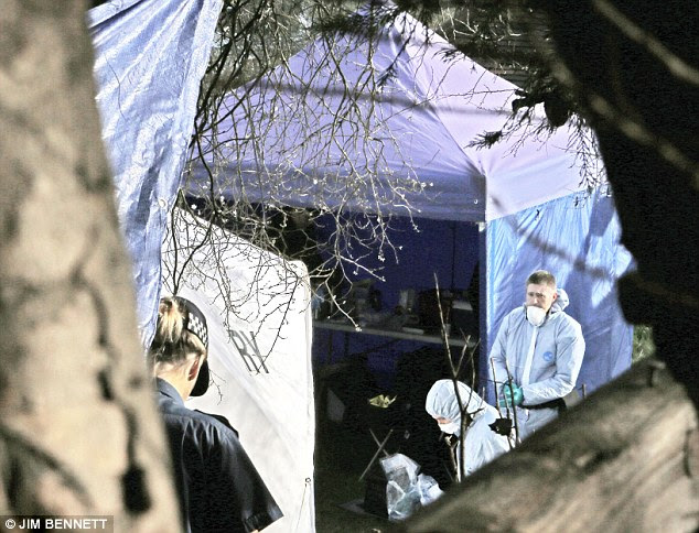 Tent: Forensics and a police officer are pictured in the garden in the home in Erith today as the area was dug up