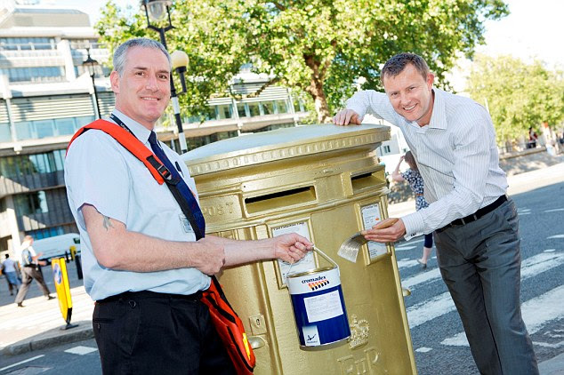 Mark Thompson (left), Olympics Director for the Royal Mail, and Paul Sheldrake apply the finishing touches to the first golden post box in Westminster