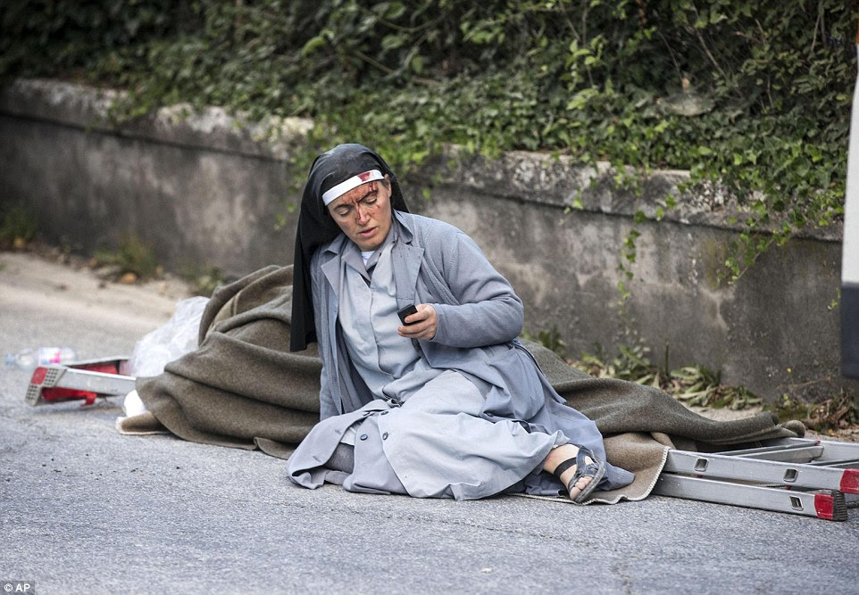 Bloodied: An injured nun checks her mobile phone as she lies near a ladder and a blanket following an earthquake in Amatrice