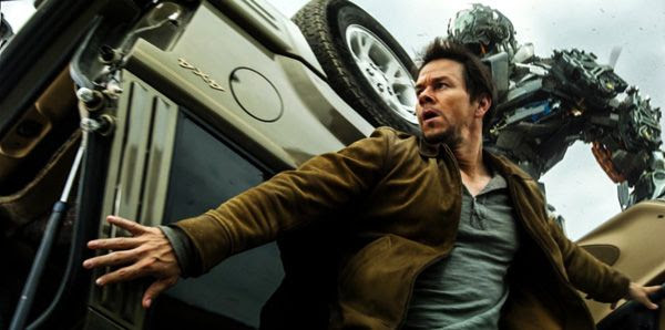 Cade Yeager hides behind a damaged vehicle as Lockdown approaches in TRANSFORMERS: AGE OF EXTINCTION.