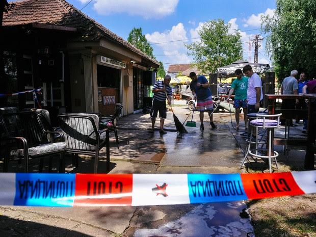 Pessoas lavam a calçada de um café onde um homem matou cinco pessoas em Zitiste, na Sérvia, neste sábado (2) (Foto: Alexa Stankovic/AFP)