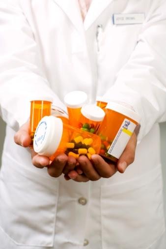 Pharmacist holding pill bottles