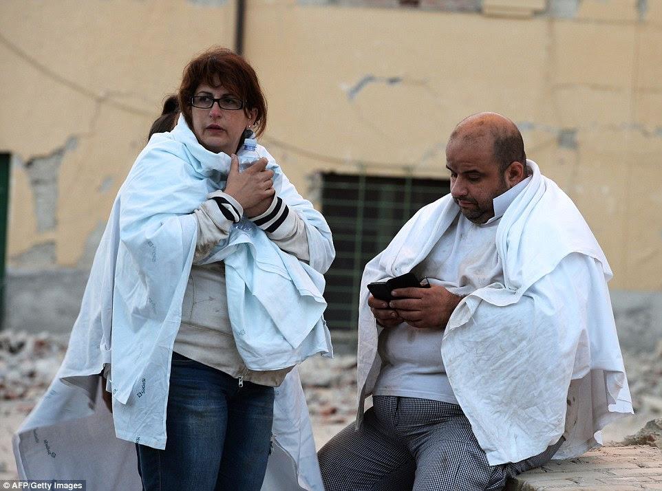 locals Truamatized tentar manter quente no início da manhã após o forte tremor sacudiu a cidade de Amatrice e grande parte da região central da Itália