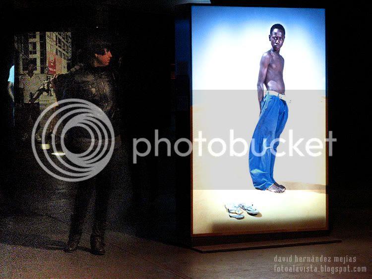 Una mujer mira en la oscuridad una fotografía de la exposición de Isabel Muñoz en la exposición de Caixa Forum, mientras el adolescente de la fotografía parece mirarla a ella en un intercambio de miradas