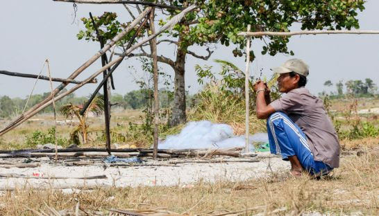 A man sits next to the remains of his house in 2014 after it was allegedly destroyed by UDG in Koh Kong province.