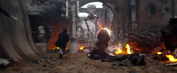 A squad of Stormtroopers and an AT-ST walker attack a Jedha village in ROGUE ONE: A STAR WARS STORY.