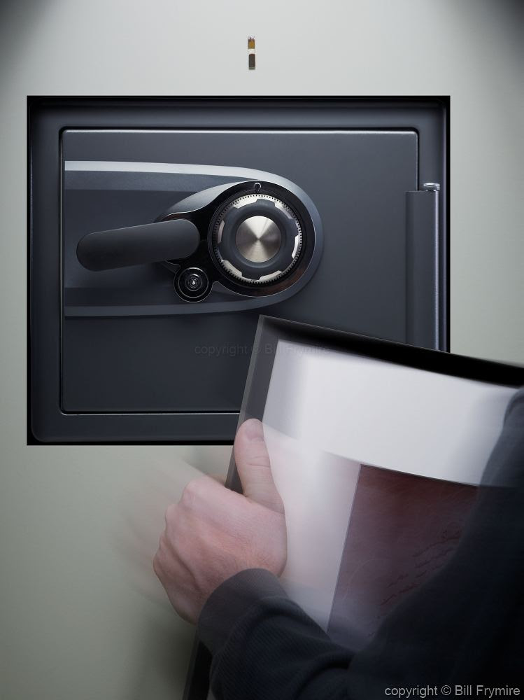 Person Revealing Wall Safe Behind Picture