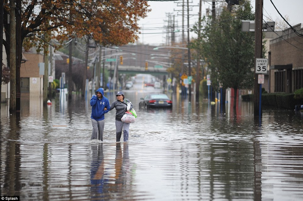 Soaked: Local residents walk through the flooded Hudson Street in Hackensack, New Jersey