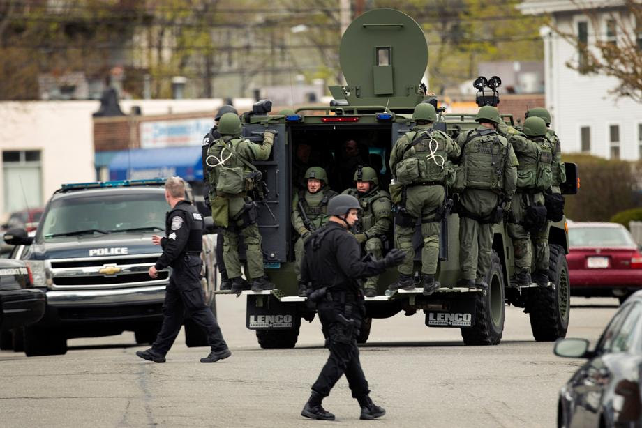 Law enforcement officers in tactical gear enter the search area for Dzhokar Tsarnaev, the one remaining suspect in the Boston Marathon bombing, in Watertown, Massachusetts April 19, 2013.
