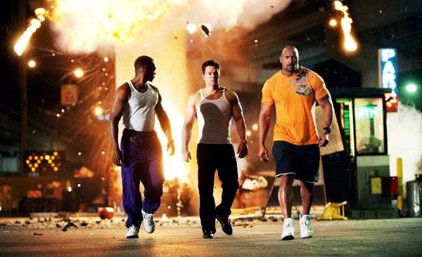 Paul Doyle (Dwayne Johnson), Daniel Lugo (Mark Wahlberg) and Adrian Doorbal (Anthony Mackie) walk away from an exploding van in PAIN & GAIN.