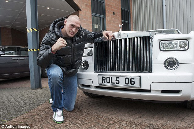 Fury poses in front of a white Rolls Royce after returning to London for his fight with Haye in 2013