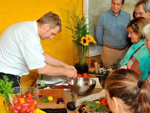 de chef staat voorovergebogen over de werktafel en is druk bezig om tomaten tot hapjes te verwerken, aan de andere kant staan bezoekers geboeid te kijken