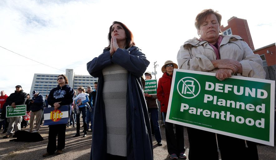 Participants in an anti-abortion rally hold signs and pray as they listen to a member of Christian clergy read from the Bible, in front of Planned Parenthood of the Rocky Mountains, in Denver, Saturday, Feb. 11, 2017. Anti-abortion activists emboldened by the new administration of President Donald Trump staged rallies around the country Saturday calling for the federal government to cut off payments to Planned Parenthood. (AP Photo/Brennan Linsley) (Associated Press)