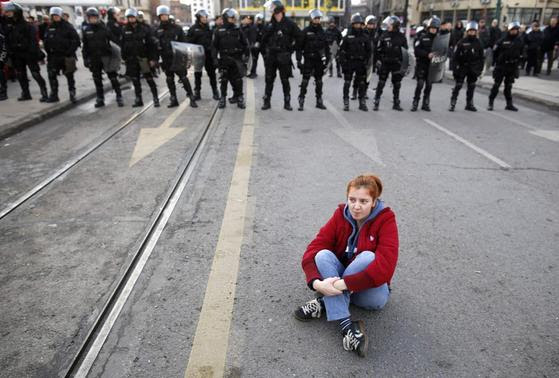 An anti-government protester sits on the ground in front of police during a demonstration in Sarajevo February 6, 2014. REUTERS/Dado Ruvic