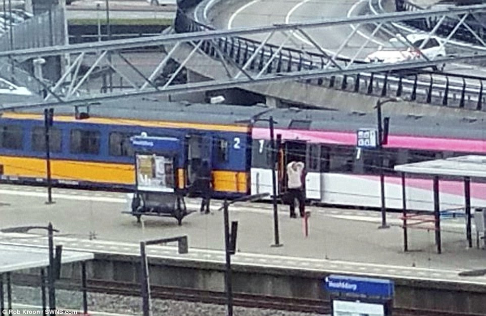 Across the border: A suspect with his hands up is arrested as he is taken off a train because of suspicious activity at Hoofddorp Station in Amsterdam