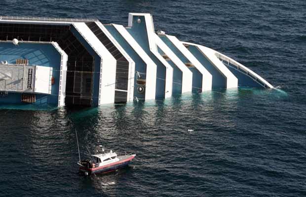 Barco dos carabineiros aproxima-se do navio de cruzeiro acidentado, neste sábado (14), na costa da Itália (Foto: AP)