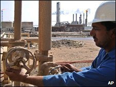 Iraqi worker operates valves at Rumaila oil field, near Basra, southern Iraq, file pic from 2005
