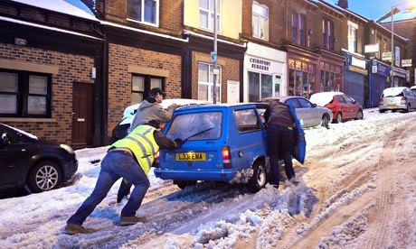 People push a car in Sheffield after the city is deluged by snow. Photograph: Tom White/PA