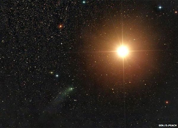 An image of comet Siding Spring (green smear at lower-left of center frame) passing by the bright orange globe of Mars...as seen by astrophotographer Damian Peach on October 19, 2014.