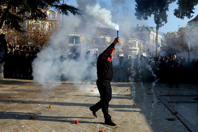 An Albanian opposition Democratic Party supporter releases a smoke flare, during a rally in front of the Parliament building, in Tirana, Albania, Thursday, D...